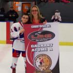 Atome A: Capitaine d'Intersport Matane reçoit la bannière de Mme Valérie Simard, vice-présidente de Hockey Matane, commandite de L2G line 2000 Matane.